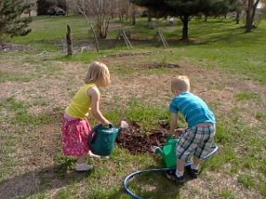 Ayden and Nadia planting a tree. Photo Credit: c.Jane H. Johann, Summer, 2013.